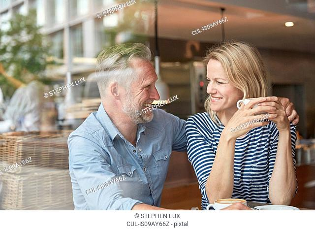 View through window of mature couple in coffee shop face to face smiling