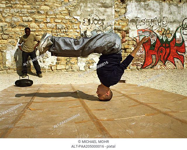 Man balancing on head, break dancing, man in background watching
