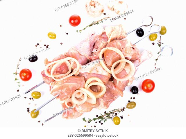 uncooked raw piece of chicken on skewers with serving spices on white background
