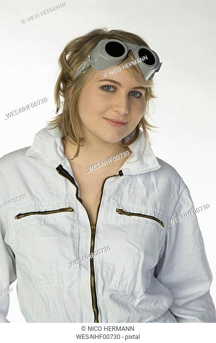 Blonde woman in overall and safety goggles, portrait