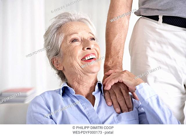 Spain, Senior couple holding hands, smiling