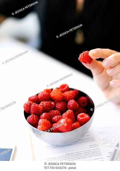 Selective focus on bowl with raspberries