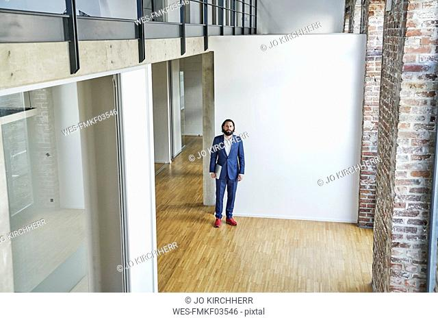 Portrait of businessman standing on empty office floor
