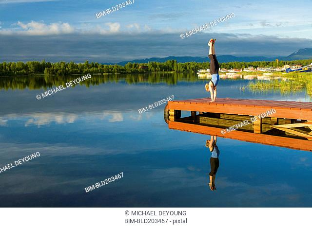 Caucasian woman practicing yoga on dock on still lake, Anchorage, Alaska, United States