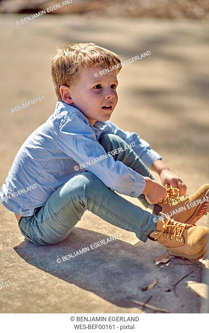 Boy sitting outdoors lacing his boots