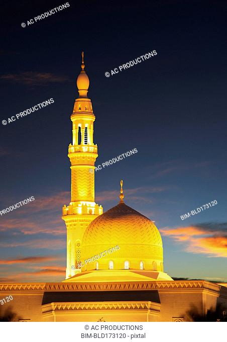 Illuminated pillar and dome under sunset sky