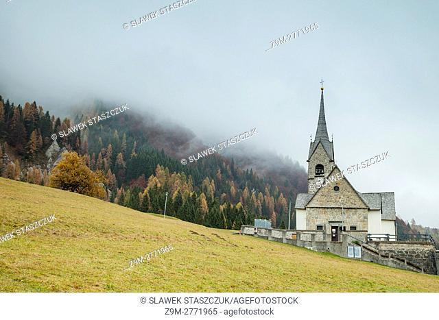 Misty autumn morning at San Lorenzo church in Sauris di Sopra, Dolomites, Italy