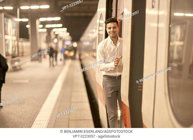 young man in door of train, at train station, in Munich, Germany