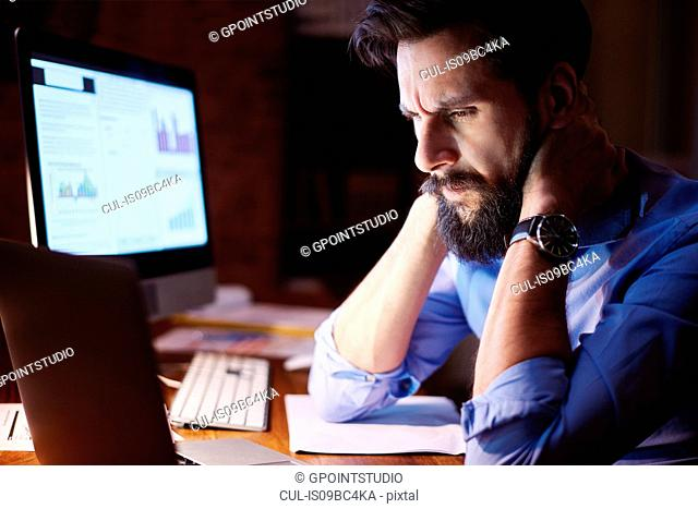 Stressed young businessman looking at laptop on office desk at night