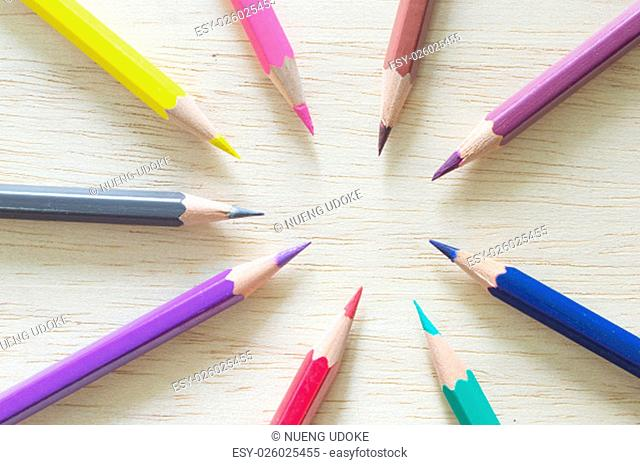 color pencils lying on the wooden background
