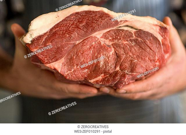 Butcher holding piece of raw meat
