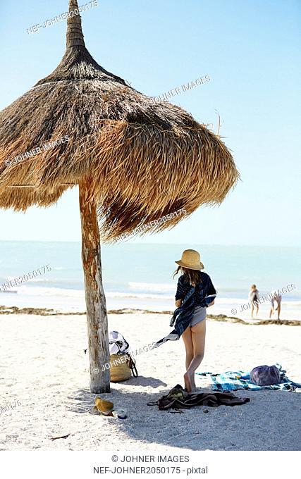 Girl standing under thatched umbrella on beach