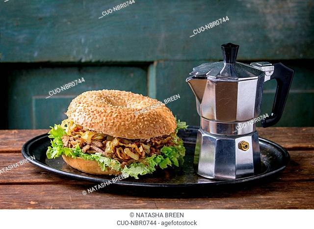 Bagel with stew beef, fresh salad and fried onion served on vintage metal tray with coffee pot over wooden table