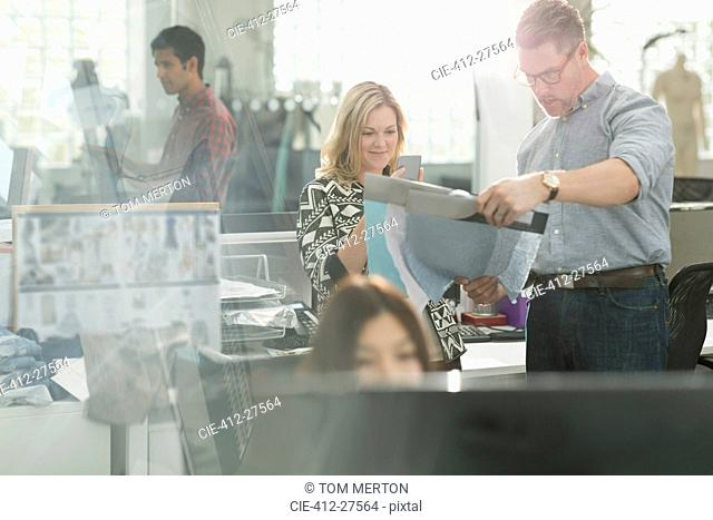 Fashion designers examining fabric in office