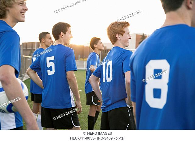 Side view of soccer players watching game on field