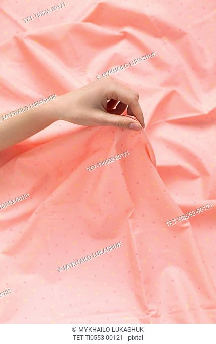 Hand of woman holding pink fabric