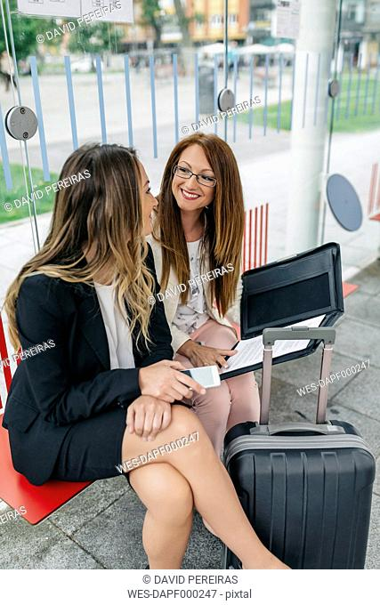 Two businesswomen at city transport stop