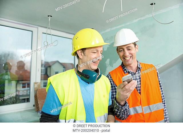 Two construction workers with smartphone at construction site of new building