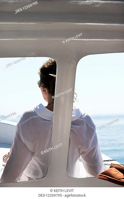 A woman in a white shirt sits at the front of a boat with a view of the ocean; Ixtapa-Zihuatanejo, Guerrero, Mexico