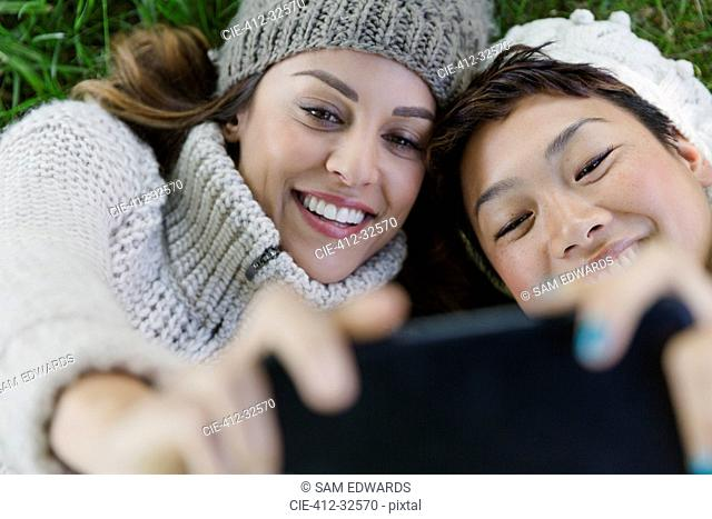 Overhead smiling female friends taking selfie with camera phone
