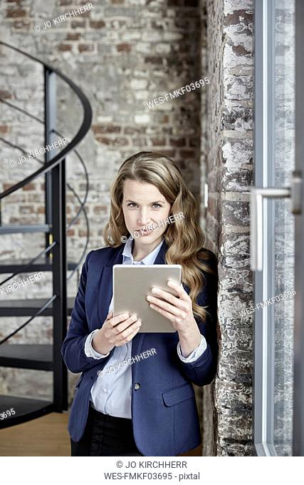 Portrait of confident businesswoman holding tablet