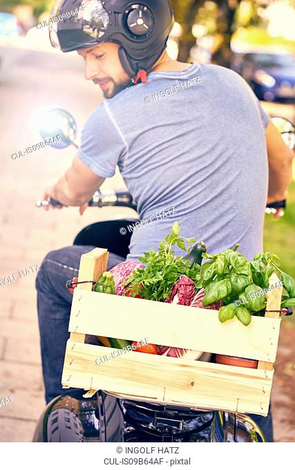 Rear view of man on motorcycling transporting vegetables in crate