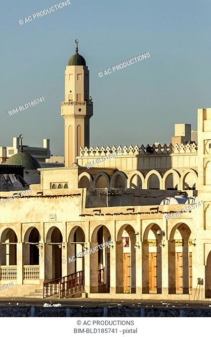 Ornate building and tower under blue sky, Doha, Qatar