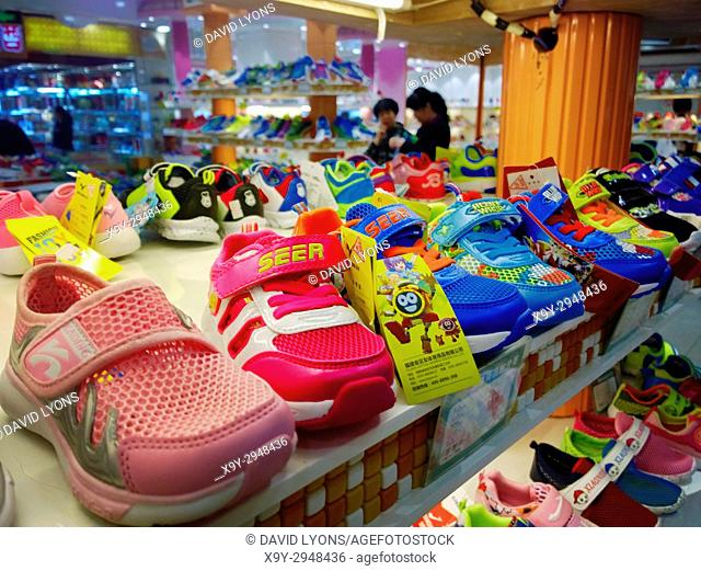 Colourful childrens infants plastic shoes trainers on display in shoe store shop in the Chinese city of Taiyuan, Shandong province, China