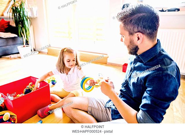 Father and daughter playing together with toys