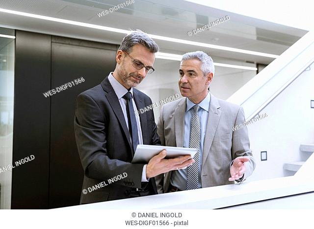 Two businessmen having an informal meeting, using digital tablet