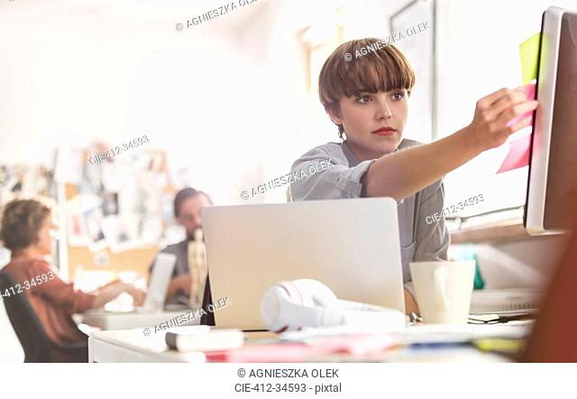 Serious female designer reviewing adhesive notes on computer in office