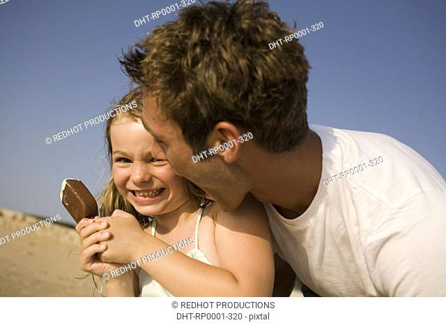 Father and daughter on beach with ice cream