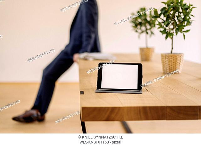 Tablet on table with businessman in background