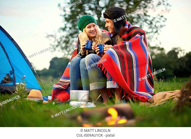 Young camping couple sitting by campfire with cup of tea