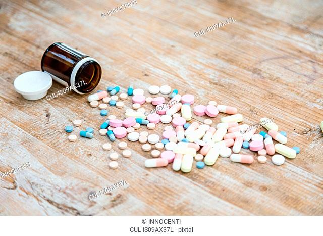Pills and pill bottle on wooden surface