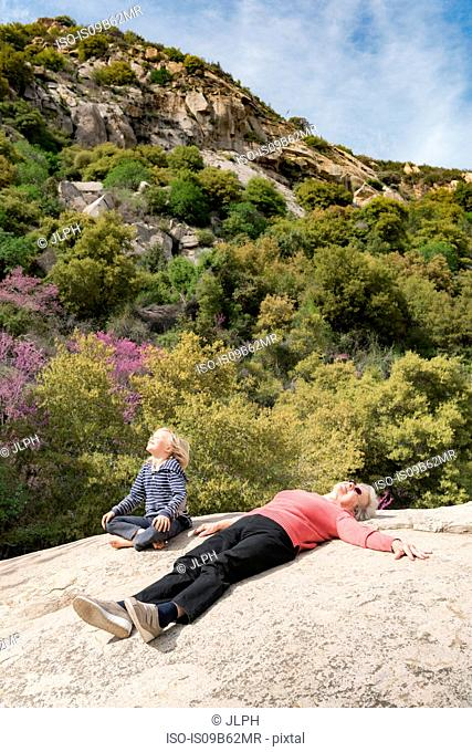 Grandson and grandmother taking break on rock, Sequoia National Park, California, US