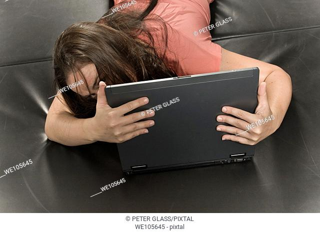 Young woman lying on a mat, working on her laptop computer