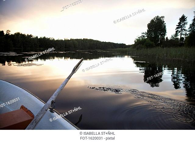 Cropped image of rowboat moored on lake during sunset