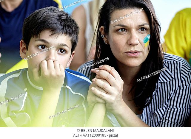 Mother and son watching football match at home