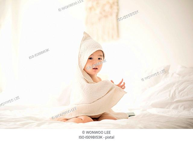 Little boy with hooded towel in bed