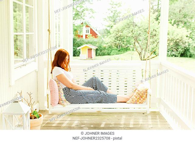 Woman sitting on swing in terrace