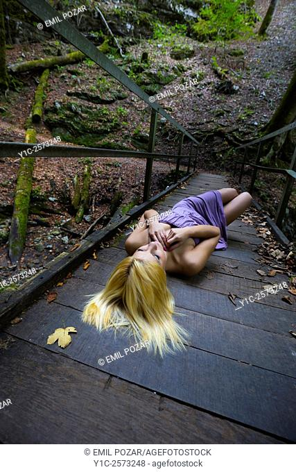 Young woman lying on wooden footbridge with spread blond hair