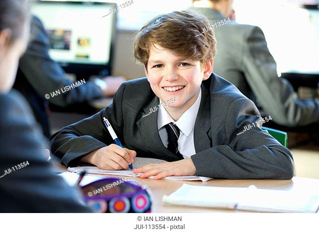 Portrait smiling middle school student doing homework in study hall