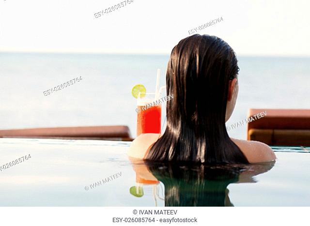 Young woman drinking Mai Thai Cocktail at the pool in a family hotel in Ko Samui, Thailand
