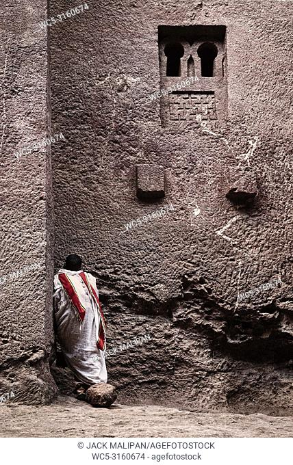 priest praying at ancient christian orthodox rock hewn church in lalibela ethiopia