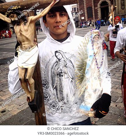 A pilgrim holds an image of Jesus Christ crucified and an image of Our Lady of Guadalupe during the annual pilgrimage to the Our Lady of Guadalupe basilica in...