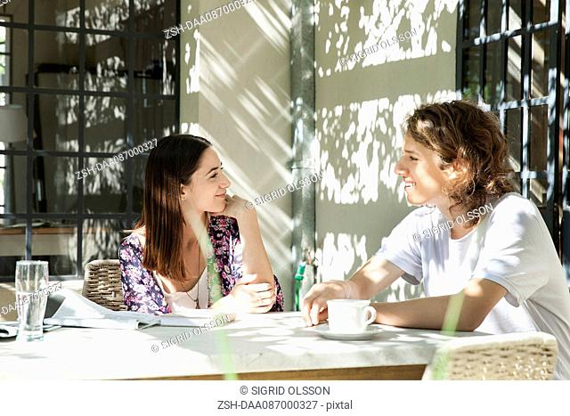 Young couple chatting at breakfast table outdoors