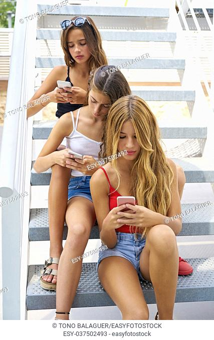Teen best friends girls in a row with smartphone having fun on stairs