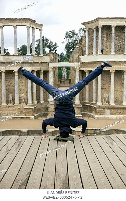 Spain, Merida, man doing a handstand with legs extended
