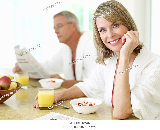 Couple in kitchen having breakfast and reading newspaper
